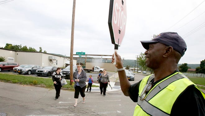 Crossing guard Robert Clark, of Elmira, stops traffic on William Street in Elmira to allow a family to safely walk to Finn Academy on the first day of school Wednesday.