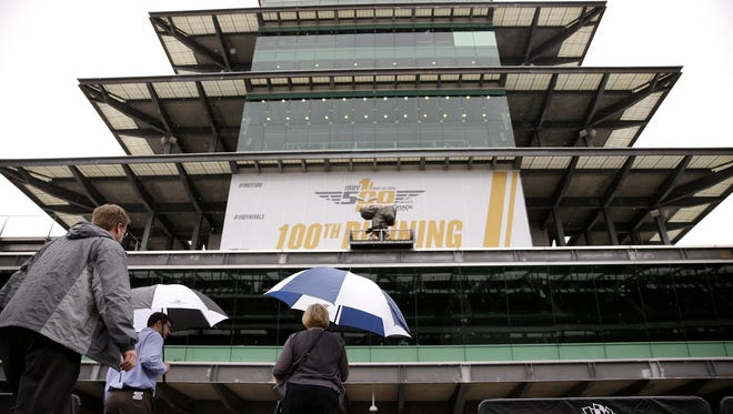 Matt Miller, Brian Stovall and Nicole Whitis make their way out of the rain at Indianapolis Motor Speedway on May 17, 2016.