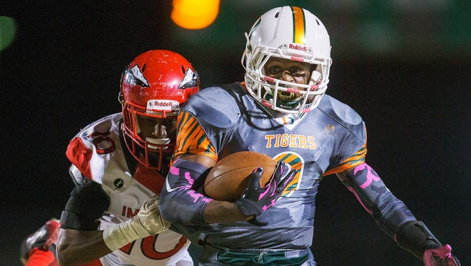 Dunbar High School's Seneca Millidge breaks free from Immokalee defenders during first quarter play Friday at Dunbar High School in Fort Myers. Dunbar beat Immokalee 41-26.