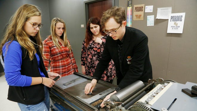 Julia Donnelly, from left, Liz Walker and Rachel Silber look on as Peter Moore locks type in the bed of a 1959 Vandercook Universal 1 proof press Thursday, November 10, 2016, in the Honors College and Residences on the campus of Purdue University. The Honors College and the College of Liberal Arts refurbished the press to create a print laboratory. Moore is Postdoctoral Teaching Fellow and Assistant Director of the Honors Mentor Program. Donnelly, Walker and Silber are all sophomores at Purdue.