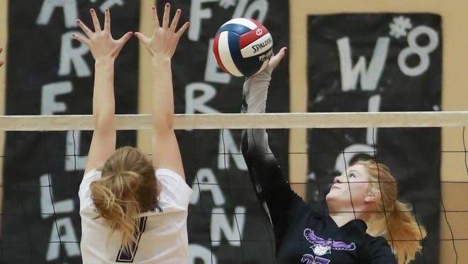 Mission Oak's Christa Pilgrim (27) spikes against Woodcrest Christian's Natalie Grover (7) during a first-round CIF State high school girls volleyball playoff game.