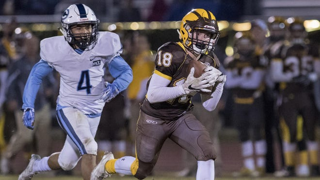 Golden West's Ian Kelly takes a pass in stride ahead of Central Valley Christian's Jaalen Rening in Friday's Central Section Division IV quarterfinal game at Groppetti Automotive Visalia Community Stadium. Kelly scored on the play.