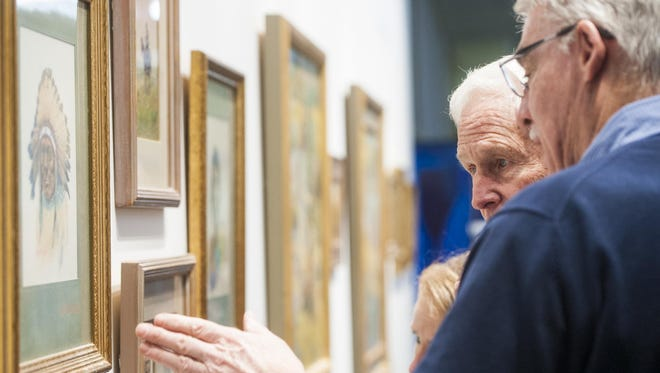 Steve Seltzer talks to Dayton Colstad during the Seltzer Gallery's opening day at C.M. Russell High School on Friday. The event showed original pieces from four generations of the Seltzer family, including O.C. Seltzer, a C.M. Russell contemporary.