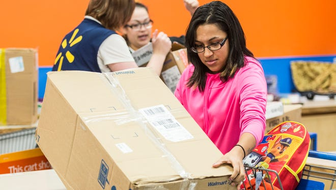 Amanda Avila, one of the lucky people to have her layaway bill paid off, loads up some of her items after a Secret Santa paid off $46,000 worth of layaway bills at the Wal-Mart located in North Lebanon Township on Monday, Dec. 12, 2016.