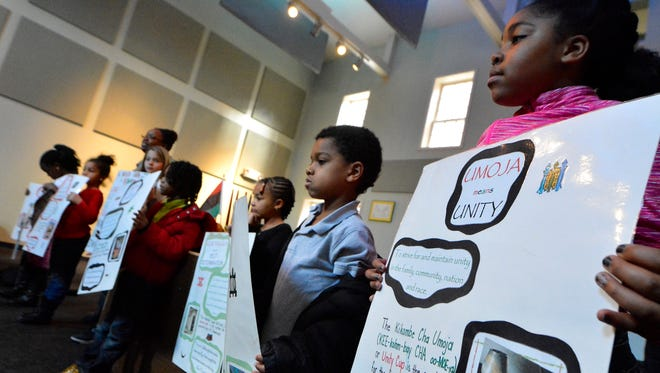 Children from the YWCA's school age program learn about Kwanza at the Martin Library, Friday, December 30, 2016.  This is the 50th anniversary of Kwanza, an African American and pan-American holiday celebrating family, community and culture.John A. Pavoncello photo