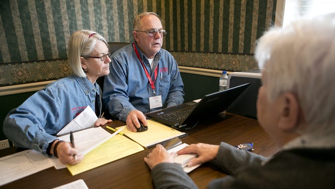 Tax volunteers, Cathy Miller-Temme, right, and Bernie Wahl, left, help Marge Nelson of Marshfield do her taxes at the Marshfield Area United Way, Friday, Feb. 13, 2015.