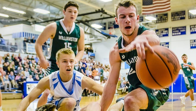 Sy Barnett, right, of Williamston and Nick Baker, bottom, of Lansing Catholic go after a loose ball during their game on December 9, 2016 in Lansing. Barnett, a senior, is thriving for the Hornets after sitting out last year due to transfer rules.