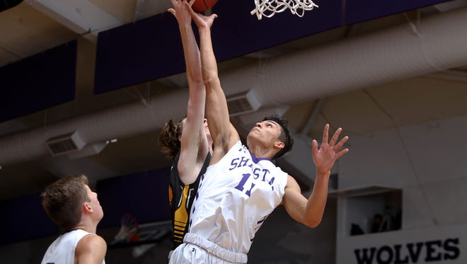 Shasta's Simer Singh, center, goes up for a rebound against Enterprise's Ian Perry in the Wolves' 47-44 win on Thursday.