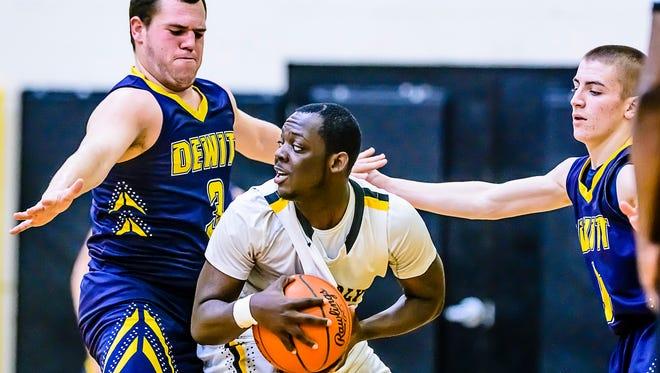 Tyshon Harris ,center, of Waverly looks to pass out of a double team by Caleb Randall ,left, and Nathan Flannery ,right, of DeWitt during their game Friday February 10, 2017 in Delta Township.  KEVIN W. FOWLER PHOTO