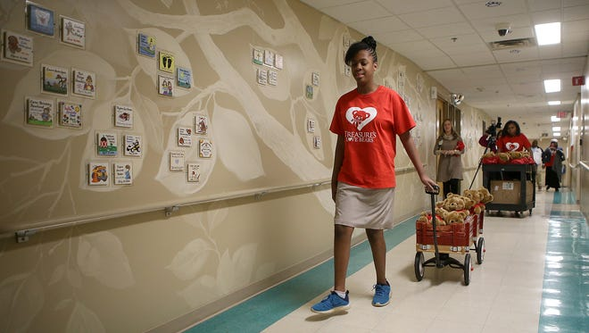 Treasure Thaxton pulls a wagon filled with Treasure's Love Bears down the hallway at Jackson-Madison County General Hospital on Valentine's Day.