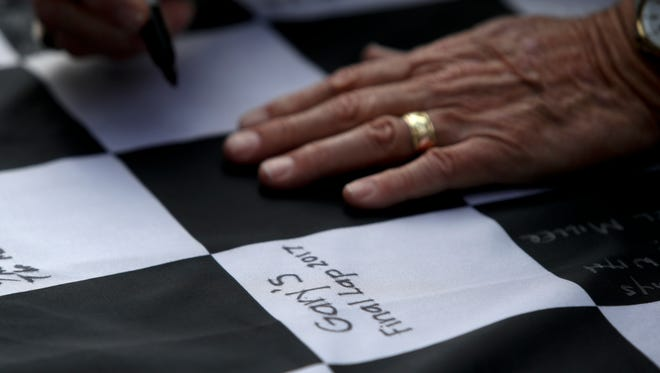 Friends and family of the late Gary Cressey sign a checkered flag on Friday at Shasta Speedway.