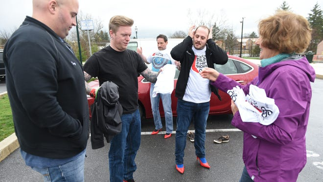 Marge Schollaert, right, Walk in Her Shoes event coordinator, gives T-shirts to Verstandig Broadcasting personalities Tiny, left, A.J. Silver, Crash Young and Xander. This year's event will be held on May 5 at 6 p.m.