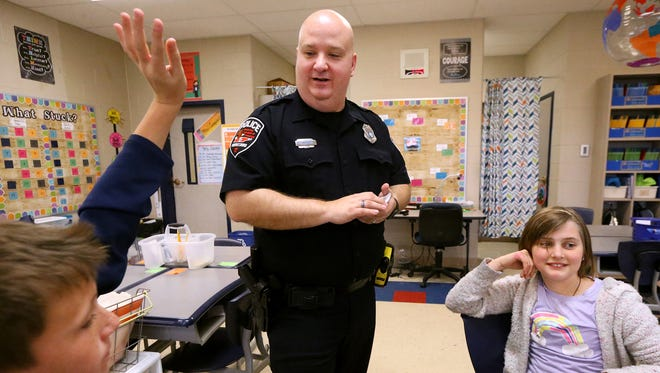 School Safety Education Officer Jay Radzinski, center,  with the Murfreesboro Police Department asks fifth grade teacher Kaitlyn Campbell's class questions about DARE during the final day of the DARE program for the Scales Elementary class, on Thursday, April 6, 2017. Lucas Cornell, left raises his hand to answer the question as Lucy Simonsen, right, tries to think of the answer.
