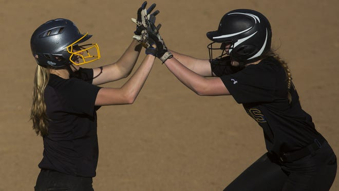 Kennard-Dale teammates Lexie Kopko, left, and Alexis Hurley celebrate after Kopko scored a run in the District 3 Class 4A softball championship game.