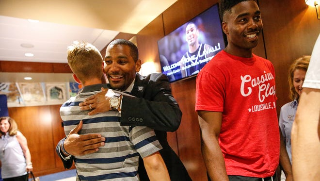 After being introduced as the Butler University head men's basketball coach, LaVall Jordan, middle, gives a hug to oncoming walk-on Campbell Donovan at Hinkle Fieldhouse on Wednesday, June 14, 2017.