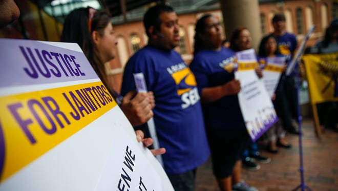 Omar Jimenez, an organizer with SEIU Local 1 in Cincinnati, translates for Ana Molina, a janitor that was let go from the Gold Building, as she talks about her former company's agreement to hire 'responsible contractors' during a rally at City Market on Thursday, July 13, 2017.