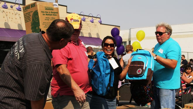 In this 2012 file photo, volunteers Dan and Bob Watson and Dave and Falicia Morgan have a blast as they pass out backpacks at the Rescue Mission's Back to School Rally.