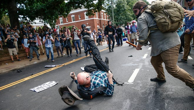 A white nationalist is knocked unconscious by a counter protester at Emancipation Park, formerly known as Lee Park, during the 'Unite the Right' rally in Charlottesville, Va., on Saturday, August 12, 2017.