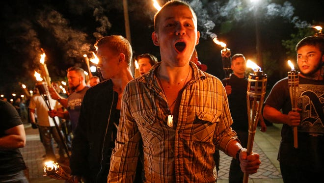 In this photo taken Friday, Aug. 11, 2017, multiple white nationalist groups march with torches through the UVA campus in Charlottesville, Va.   Hundreds of people chanted, threw punches, hurled water bottles and unleashed chemical sprays on each other Saturday after violence erupted at a white nationalist rally in Virginia.