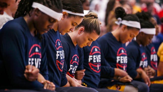 Indiana Fever teammates kneel during the national anthem before the game against the Phoenix Mercury at Bankers Life Fieldhouse on Sept. 21, 2016.