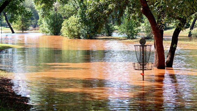 Hole No. 3 of the Lucy Park disc golf course sticks out of a flooded, low-lying area of the park Monday morning after the Wichita River overflowed its banks following the area's recent rains.