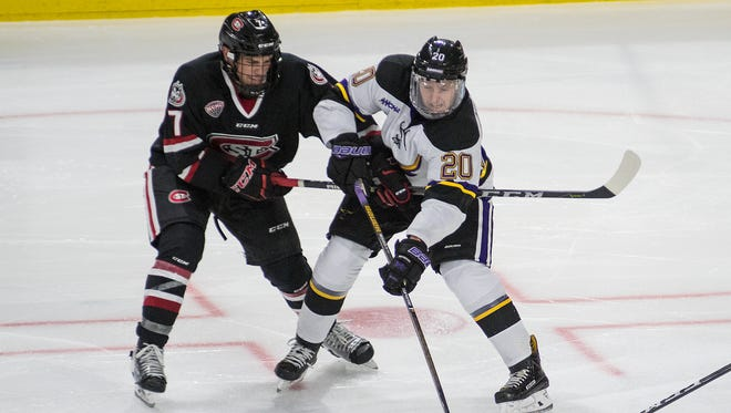 Marc Michaelis (20) of Minnesota State makes a pass to a teammate while being defended by Nick Poehling (7) of St. Cloud State. MSU lost to St. Cloud 3-0 in their home opener.