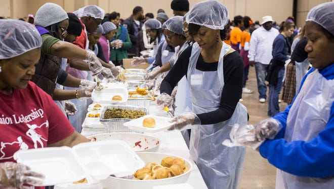 November 23, 2017 - Precious Harris, second from left, serves up cranberries while getting a plate together during the 33rd annual Memphis Thanksgiving Dinner for the Homeless and Hungry at the Cook Convention Center.