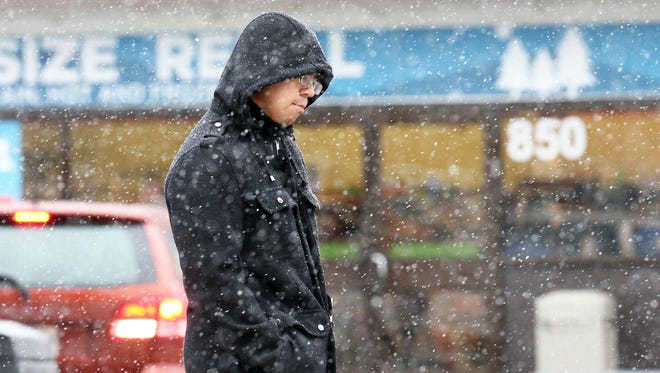 Juan Cano of El Paso walks along the 800 block of South Zaragoza Road amid snow flurries Thursday. Cano said the weather reminds him of growing up in Colorado.