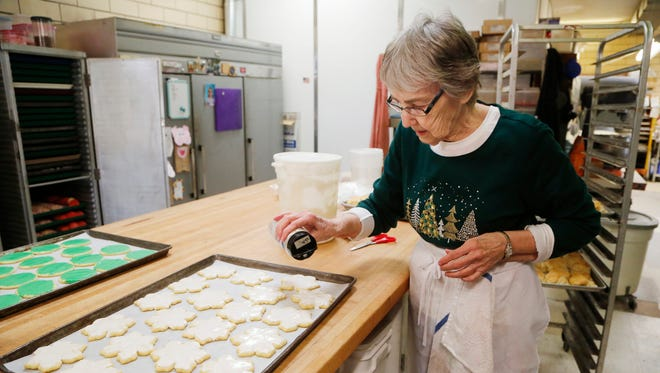 """Mary Freitag decorates snowflake Christmas cookies Thursday, December 14, 2017, at O'Rears Pastry Shop, 321 N. Ninth Street in Lafayette. Freitag said 25 different varieties of Christmas cookies are baked at O'Rears for the holidays. """"It's my favorite time of year,"""" she said."""