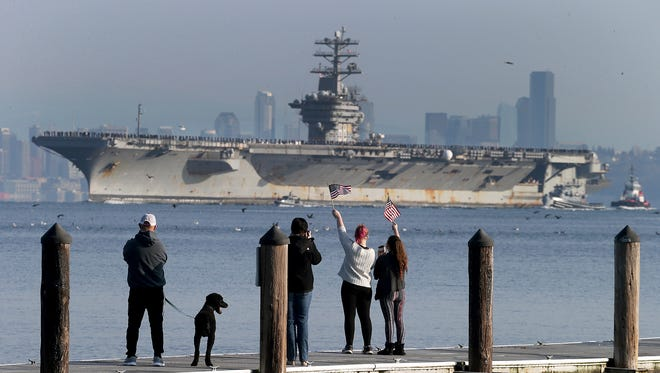The USS Nimitz returns from a deployment as people wave from the Manchester Pier on Sunday.