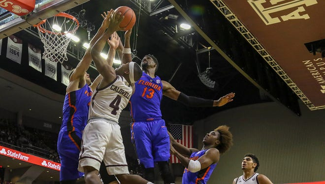 Texas A&M Aggies guard JJ Caldwell (4) shoots over Florida Gators guard Egor Koulechov (4) and forward Kevarrius Hayes (13) during the second half at Reed Arena.