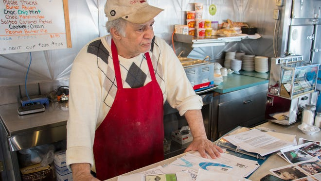 Owner of Lee's Diner Omar Ilayan lays out paperwork from past failed inspections.