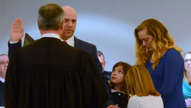 John Snyder's daughters Sophie, 8, Abby, 8, and Taylor, 17, right, hold the Bible as MDJ Keith Albright administers the Oath of Office to West Manchester Township's new Police Chief, Thursday, February 22, 2018. Officers from Snyder's former department, Newberry Township, along with West Manchester and other local law enforcement officers were on hand to witness Chief Snyder's swearing-in. Snyder will start his new position March 5.