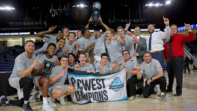 The Dixie State's Men's Basketball team poses after winning the 2018 Pacific West Conference Tournament title.