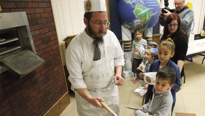 Rabbi Levi Greenberg, associate rabbi at Chabad Lubavitch, 6615 Westwind Drive, takes a freshly baked matzah out of the oven for children enrolled in the Chabad Education Center's spring camp in March 2018. About 20 children learned how to make the unleavened flatbread in a model matzah bakery while learning about its historical significance with Passover, the Jewish holiday that commemorates the redemption from Egypt 3,330 years ago, Greenberg said. Matzah serves as the primary symbol of the redemption and is eaten during Passover observances.
