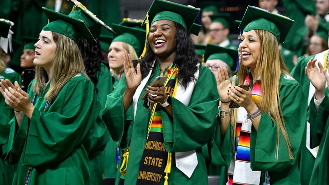 """Members of the Michigan State University Class of 2018 sing """"Victory for MSU,"""" formerly called """"MSU Fight Song,"""" Friday, May 4, 2018, during the 2018 Spring Convocation at the Jack Breslin Student Events Center in East Lansing."""