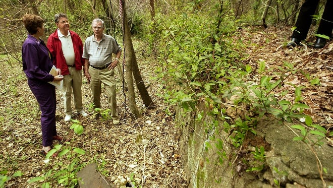 From left, Pam Shucker, Rip Turner and Ed Isler stand in what used to be the swimming lake at Dreamland Friday April 4, 2003. The lake was located off Poinsett Highway.