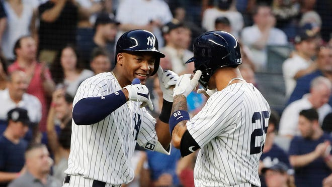 New York Yankees' Miguel Andujar, left, celebrates with teammate Gleyber Torres after Torres hit a three run home run.