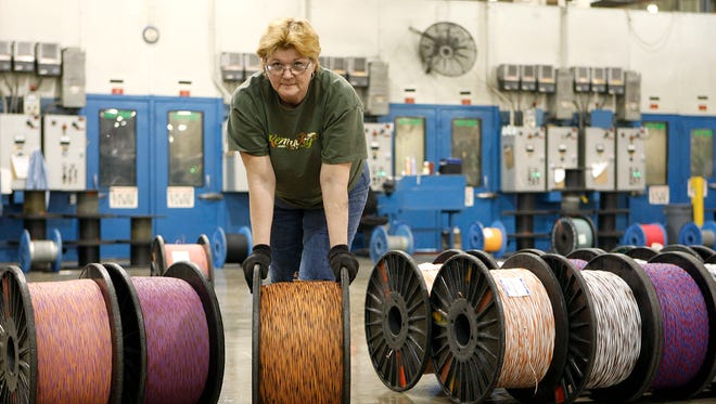 Wanda Cloran rolls a large bobbin of telephone-line wire at General Cable's manufacturing plant in Lawrenceburg, Ky. Analysts say General Cable has at least another year of restructuring as it cuts 1,000 jobs worldwide and sells off factories.