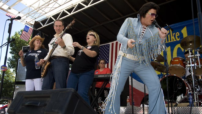 "Former Arkansas Gov. Mike Huckabee plays with his band, Capital Offense, as an Elvis impersonator helps out with a rendition of ""Johnny B. Goode"" at the Iowa Straw Poll in Ames in August 2007."