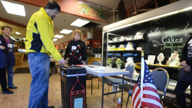 A voter drops off his ballot at Harmony Market on Tuesday Nov. 4, 2014.
