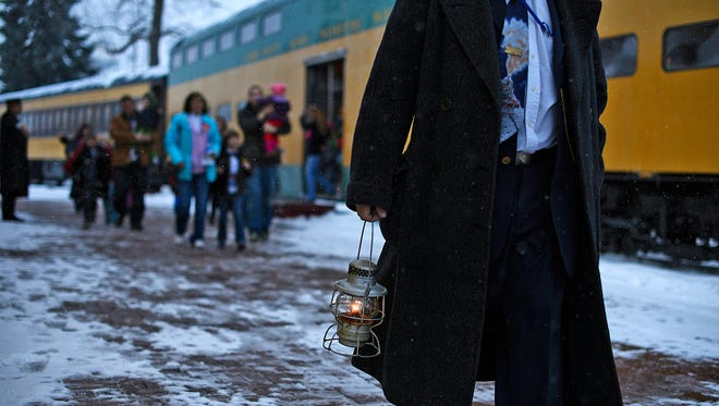 A conductor leads a pack of festivalgoers during The Polar Express event at the National Railroad Museum in Ashwaubenon.