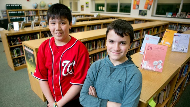 Eighth-grader Preston Hochberger, 15, left, and seventh-grader Michael Decker, 13, right, pose in the library at Colby Middle School on Tuesday. Hochberger and Decker will be competing in the national finals of the National History Bee in Louisville.