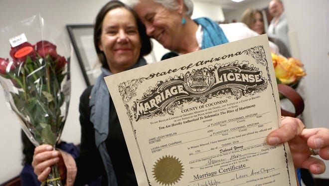 Laura Anne Chapman, left, and Jamie Whelan hold up their signed marriage certificate after becoming the second couple to be legally married in Coconino County Friday afternoon Oct. 17, 2014 in Flagstaff, Ariz. The pair who have been together for 22 years were married in Flagstaff Justice Court by Justice of the Peace Howard Grodman.