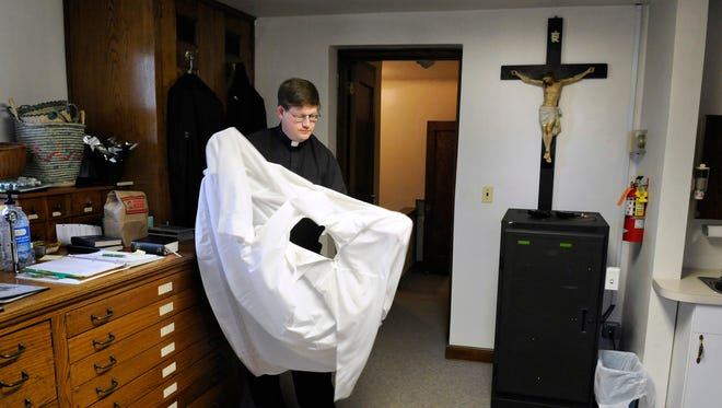 The Rev. Greg Mastey gets into his robes March 29 for his second Palm Sunday Mass.