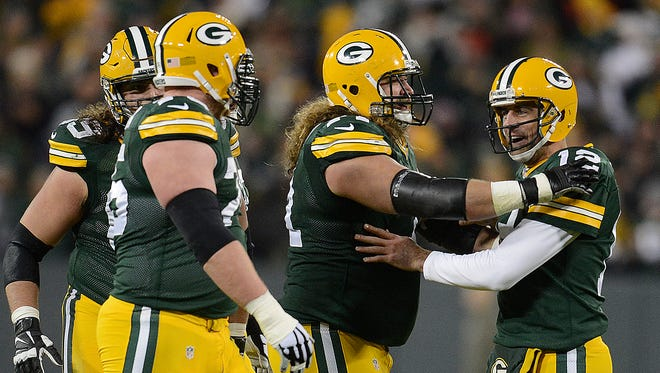 Green Bay Packers quarterback Aaron Rodgers (12), right, celebrates a touchdown with his offensive linemen against the Chicago Bears.