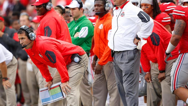 Ohio State co-defensive coordinator Luke Fickell (left) elected to stay with Urban Meyer and the Buckeyes through the playoffs while also working at his new job as head coach at the University of Cincinnati.