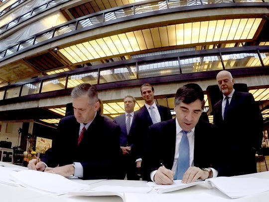 JCP&L President Jim Fakult (left) and Somerset Development President Ralph Zucker sign a lease agreement Thursday, October 27, 2016, for space at the Bell Works facility in Holmdel.
