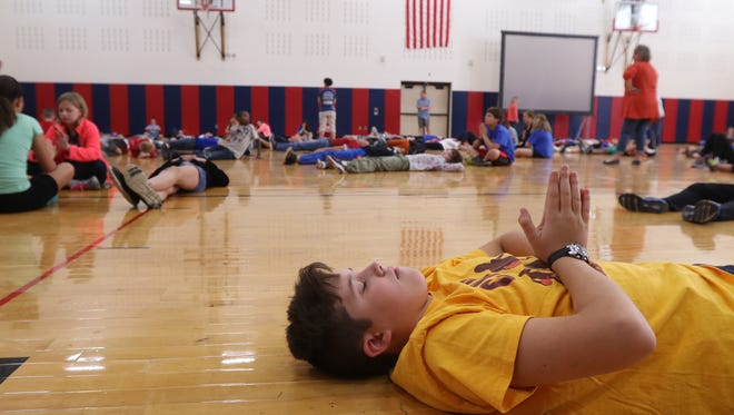 Johanna Perrin Middle School had a schoolwide mindfulness activity with students rotating through yoga and meditation. Hayden McCue with fellow sixth-graders end their yoga with breathing.