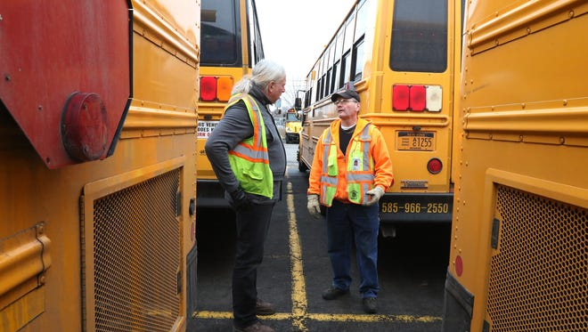Patrick Lynch tells Frank Copenhagen, driver trainer and safety coordinator with the school district, what he's doing as he does an external examination of the bus.  Copenhagen is also a certified examiner for school bus drivers.